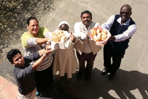 """Caritas leaders participating in a """"Food for All"""" meeting in Rome this week raise up bread. Credit: Sheahen/Caritas"""